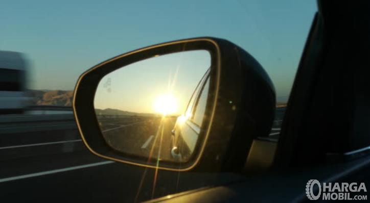 gambar ini menunjukkan spion mobil tersorot sinar matahari