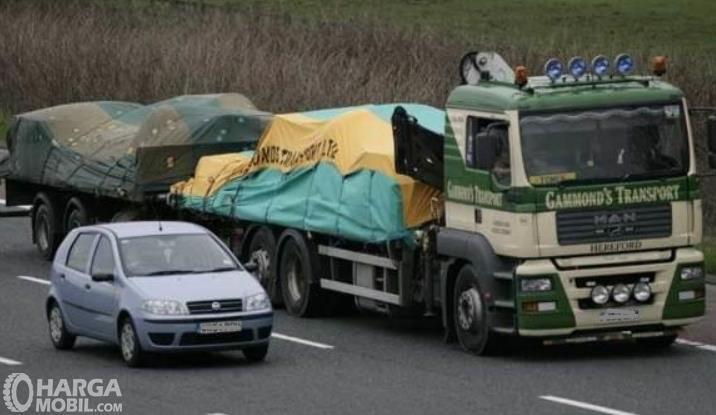 Gambar ini menunjukkan mobil Hatchback menyalip sebuah truk