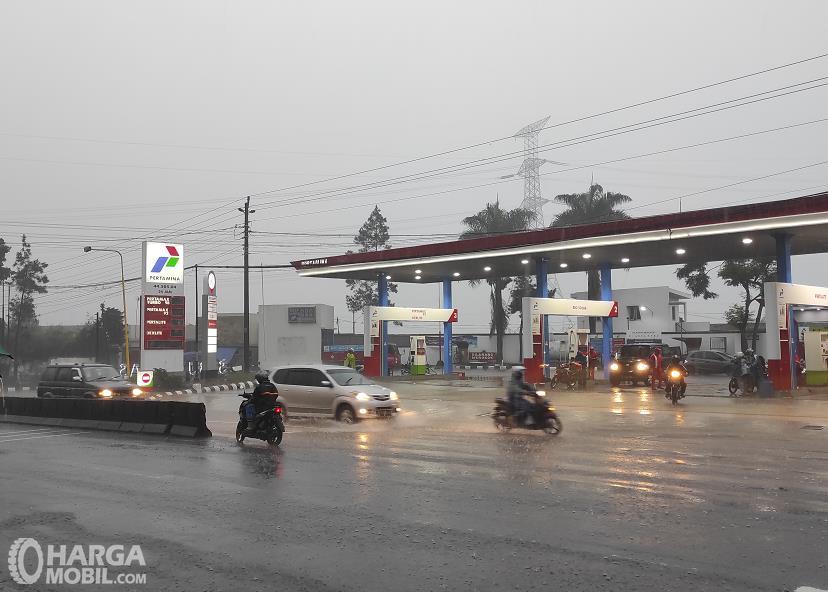 Gambar ini menunjukkan SPBU dan beberapa kendaraan di jalan kondisi hujan deras