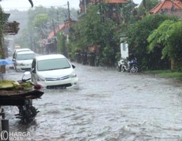 Gambar ini menunjukkan mobil menerjang banjir