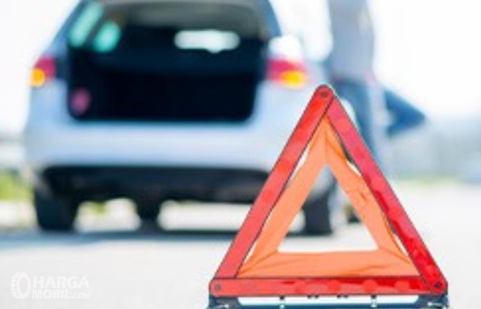 Gambar ini menunjukkan segitiga pengaman dengan mobil mobik di belakangnya