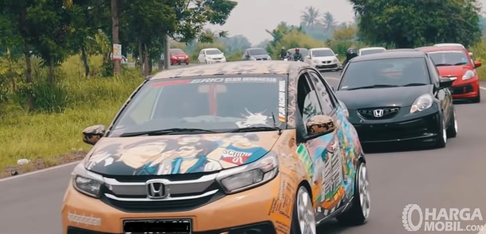 Gambar ini menunjukkan mobil Honda Brio sedang touring