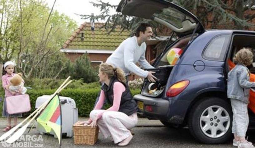 Gambar ini menunjukkan sekeluarga persiapan membawa barang di mobil