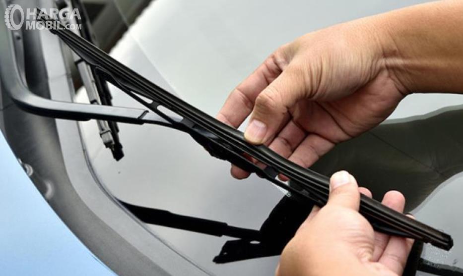 Gambar ini menunjukkan sebuah tangan memegang bilah wiper mobil