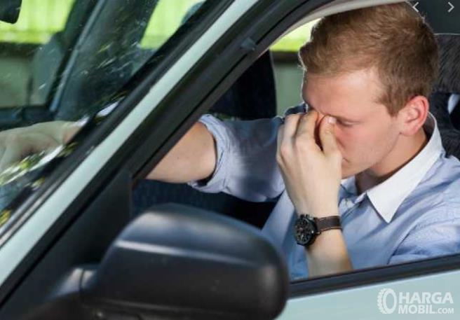 Gambar ini menunjukkan pengemudi merasa pusing