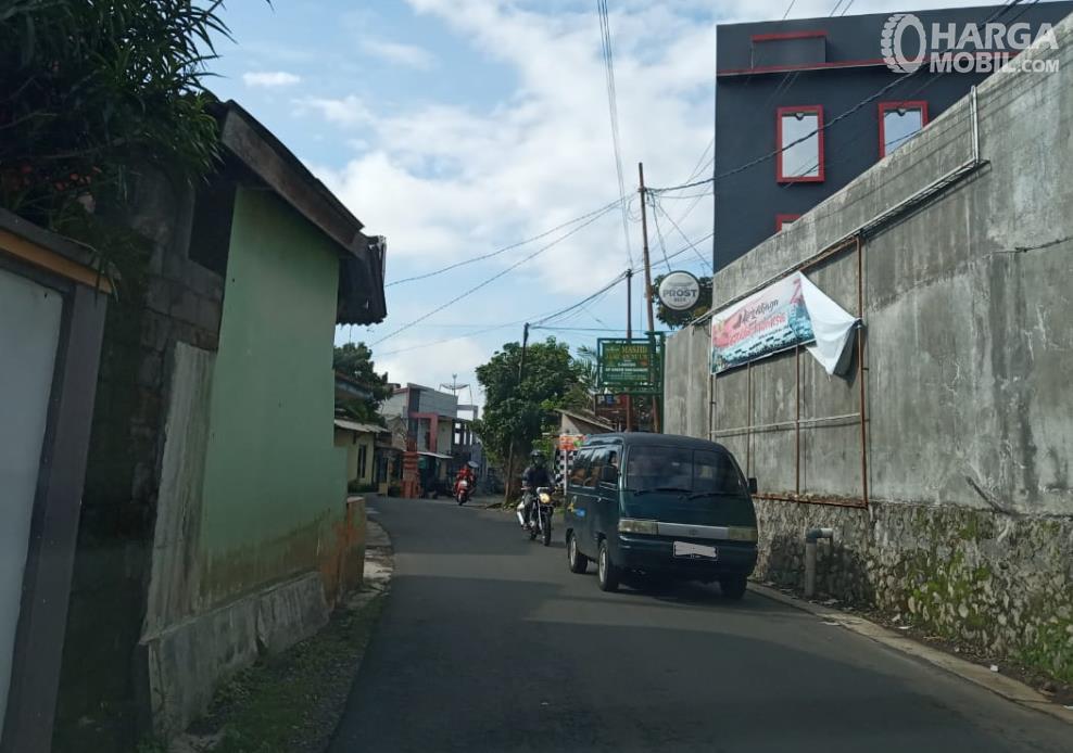 Gambar ini menunjukkan mobil melaju di jalanan kecil