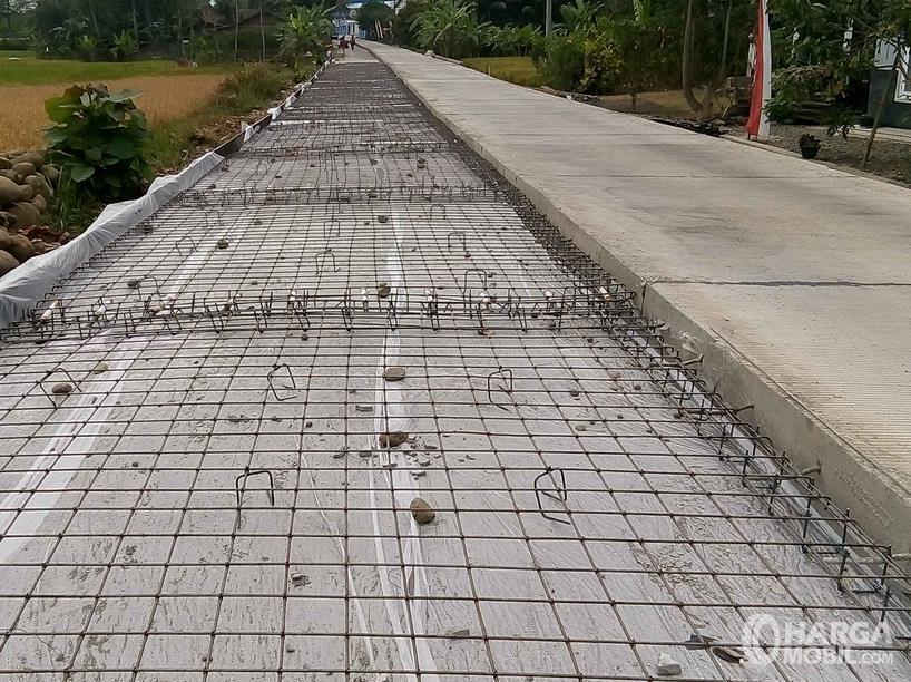 Gambar ini menunjukkan pembuatan jalanan beton