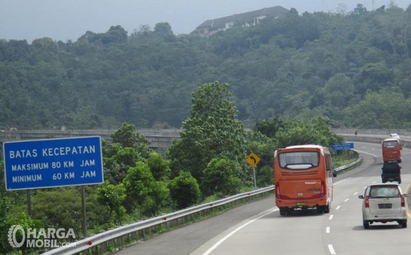 Gambar ini menunjukkan batas kecepatan di jalan Tol dan beberapa mobil