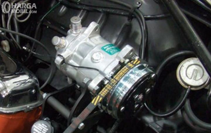 Gambar ini menunjukkan kompresor AC di dalam mesin mobil