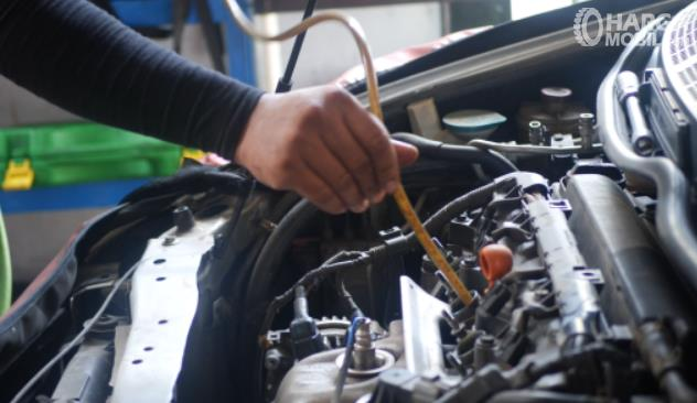 Gambar ini menunjukkan pengisian oli kompresor AC mobil