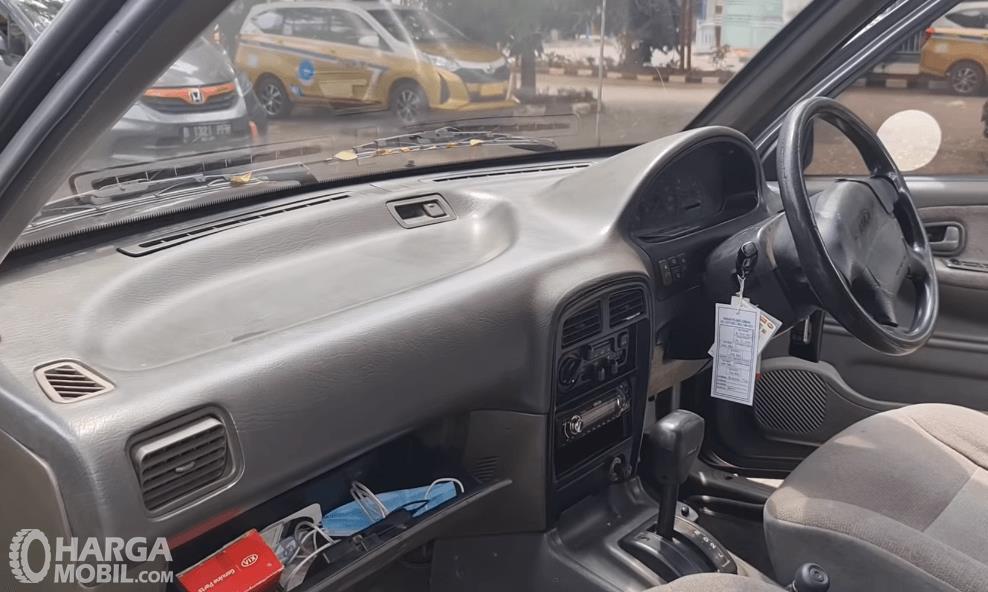 Gambar ini menunjukkan dashboard dan kemudi mobil KIA Sportage 2000
