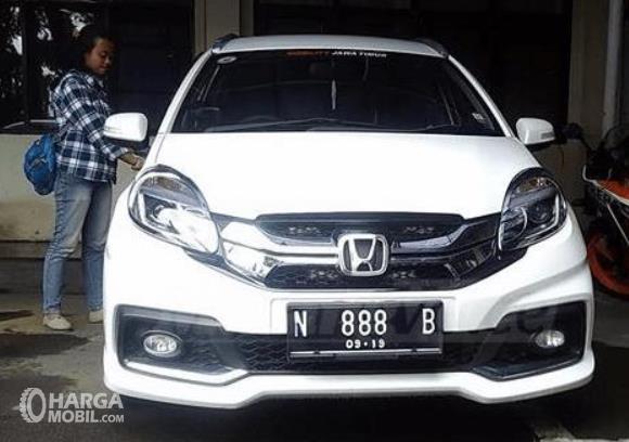 Gambar ini menunjukkan mobil putih dengan nomor cantik