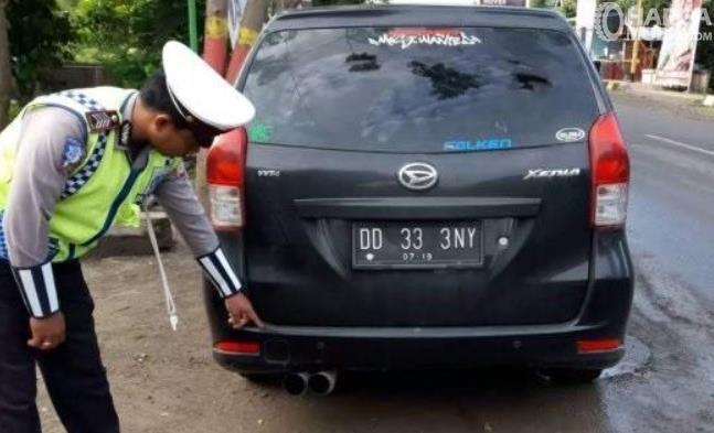 Gambar ini menunjukkan polisi berada di belakang mobil