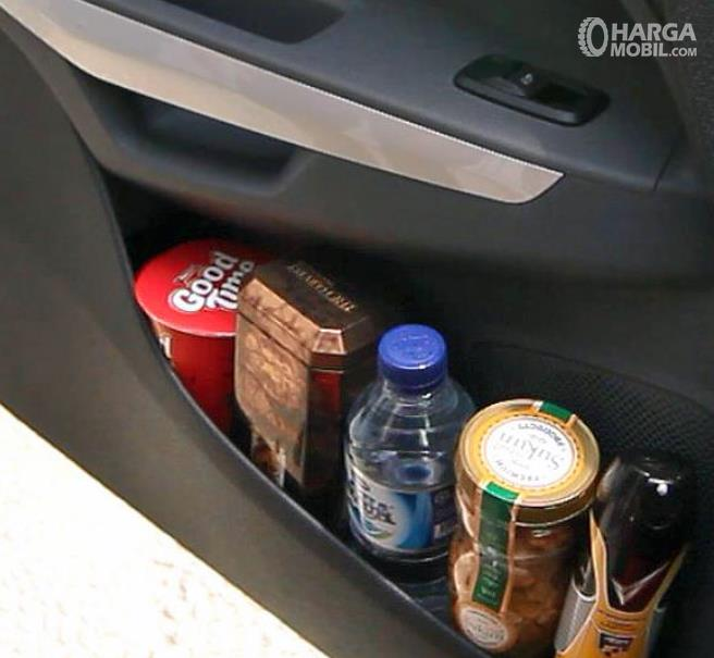 Gambar ini menunjukkan makanan dan minuman di tempat penyimpanan yang ada pada door trim pintu mobil