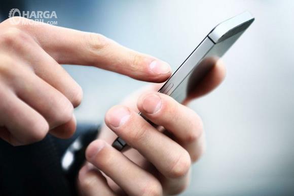 Gambar ini menunjukkan sebuah tangan memegang ponsel