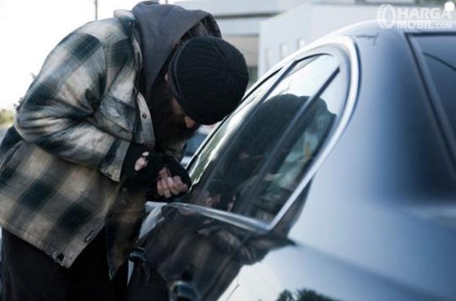 Gambar ini menunjukkan seseorang sedang mencongkel kaca mobil
