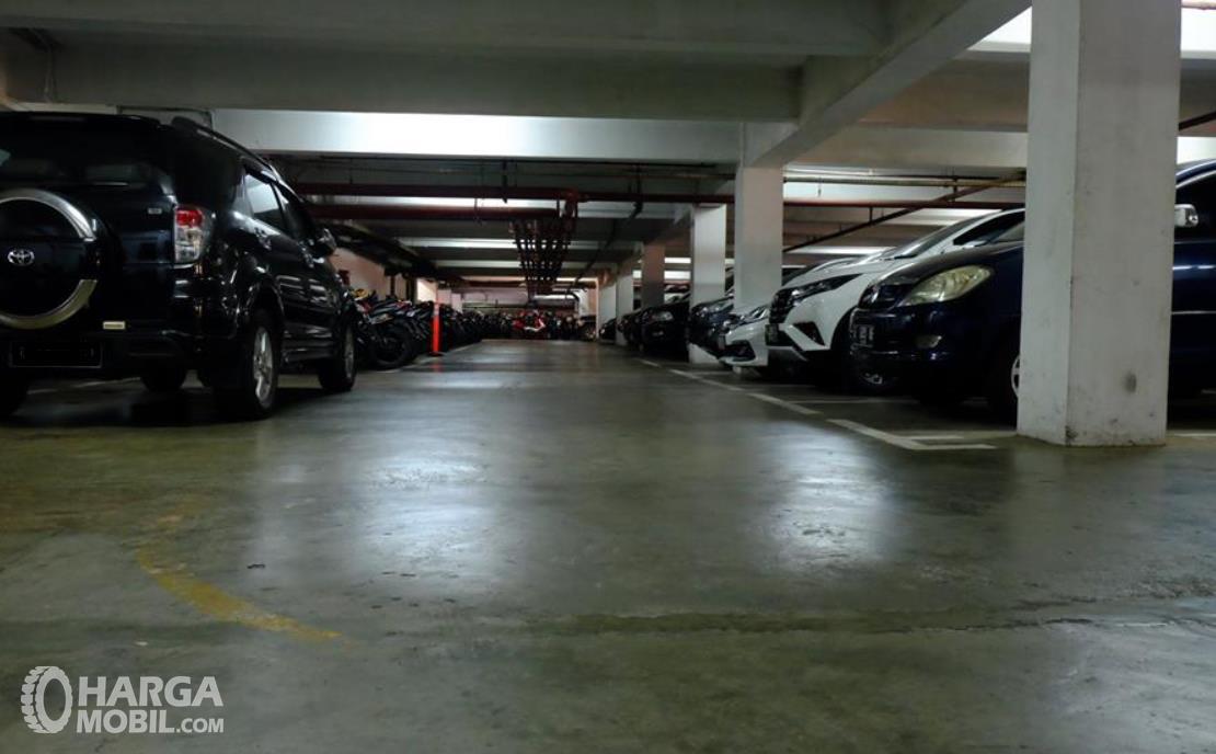 Gambar ini menunjukkan parkiran luas dengan banyak mobil