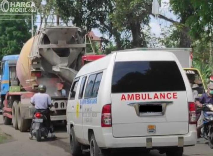 Gambar ini menunjukkan mobil ambulans yang terhalangi kendaraan lain