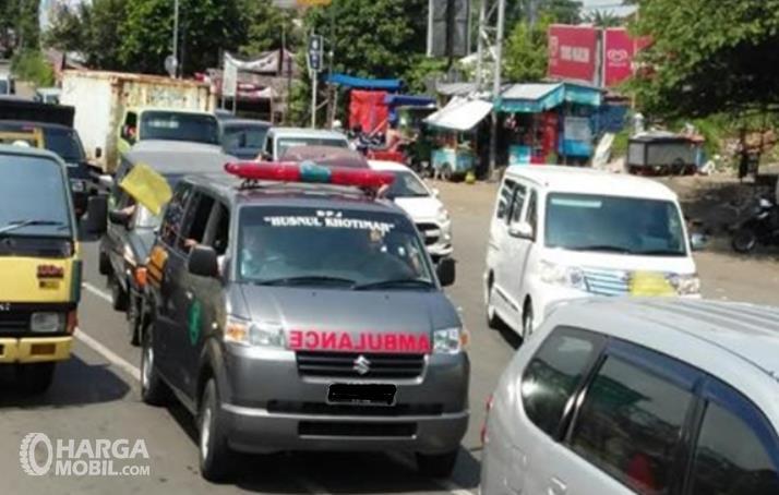 Gambar ini menunjukkan mobil ambulans terjebak dan terhalangi kendaraan lain