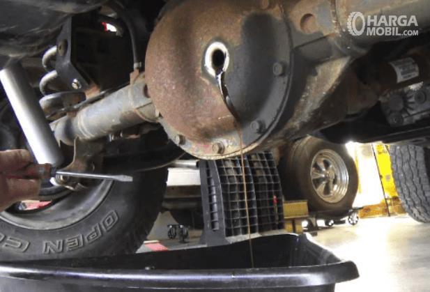 Gambar ini menunjukkan pengurasan oli gardan pada mobil