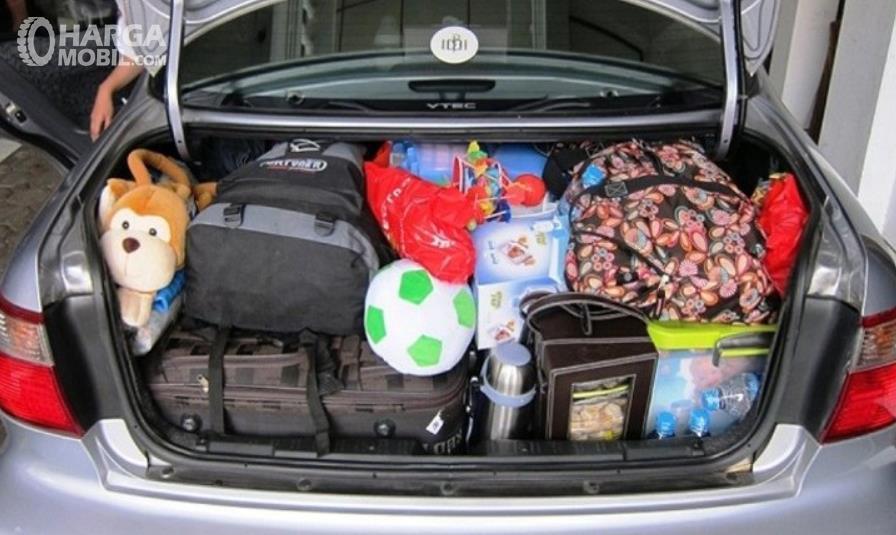Gambar ini menunjukkan barang bawaan di bagasi mobil sedan