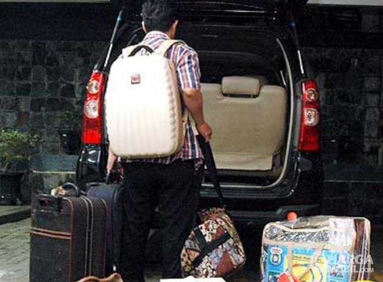 Gambar ini menunjukkan seseorang memasukkan barang di bagasi mobil