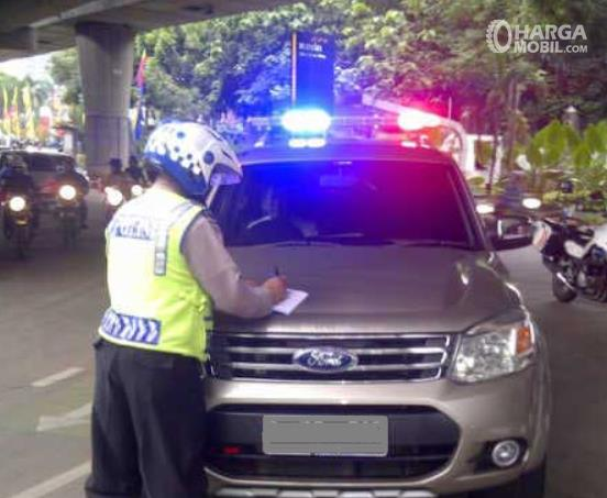 Gambar ini menunjukkan polisi menilang mobil dengan lampu rotator