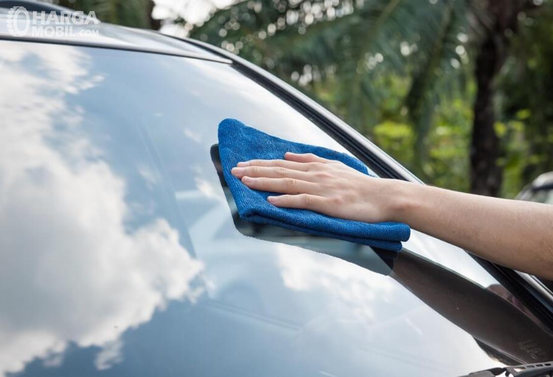 gambar ini menunjukkan pengelapan kaca mobil dengan kain
