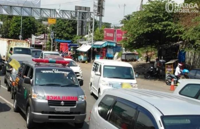 Gambar ini menunjukkan ambulans berada di jalan dengan banyak mobil