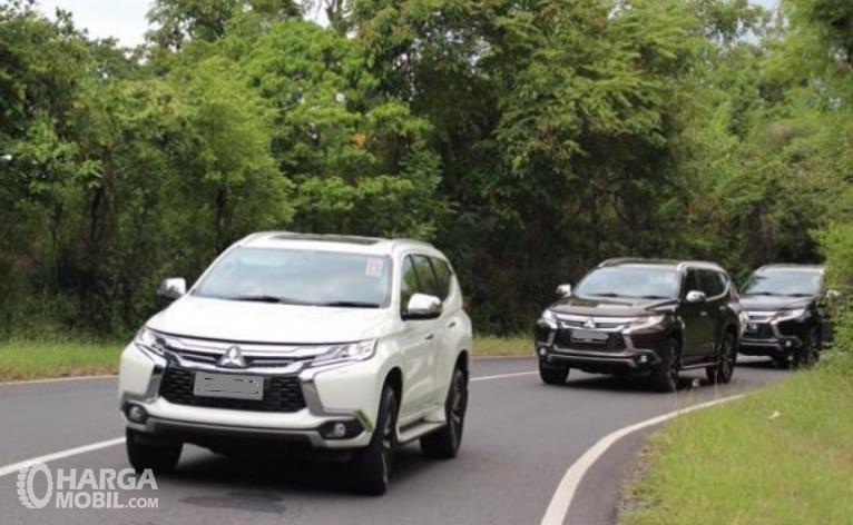 Gambar ini menunjukkan 3 mobil melaju di jalan