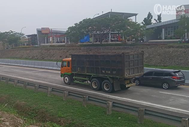 Gambar ini menunjukkan mobil hitam sedang menyalip mobil besar di jalan tol