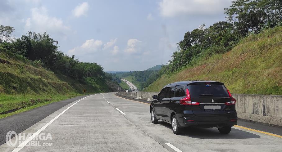 Gambar ini menunjukkan sebuah mobil melaju di lajur kanan jalan tol