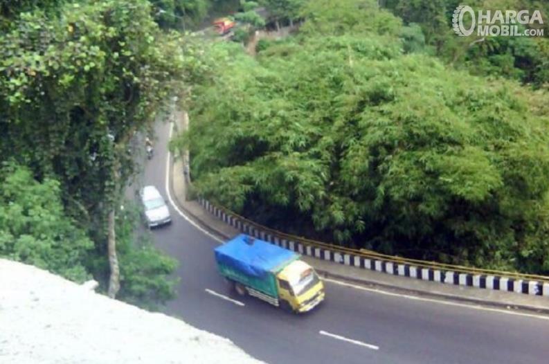 Gambar ini menunjukkan beberapa mobil melewati tanjakan