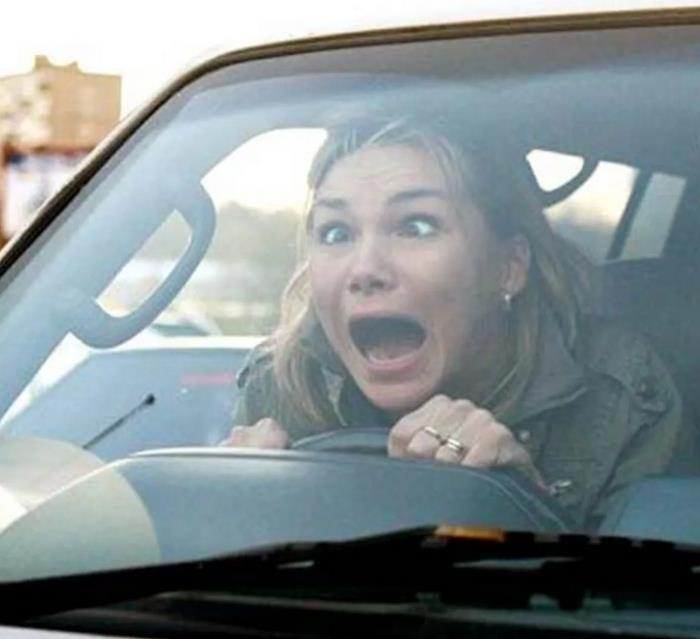 Gambar ini menunjukkan pengemudi wanita berekspresi kaget