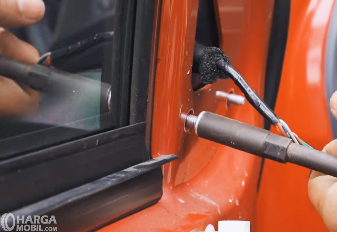 Gambar ini menunjukkan proses pelepasan baut pada spion mobil