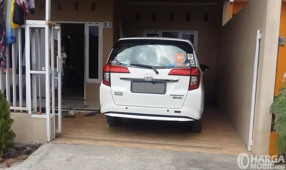 Gambar ini menunjukkan mobil tampak belakang di garasi rumah