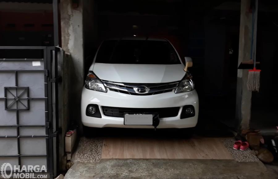 Gambar ini menunjukkan sebuah mobil warna putih di garasi