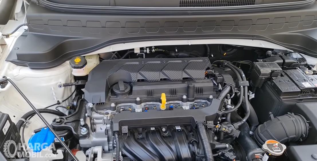 Gambar ini menunjukkan mesin mobil KIA Sonet Active 2021
