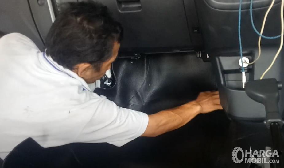 Gambar ini menunjukkan seseorang memasang karpet mobil