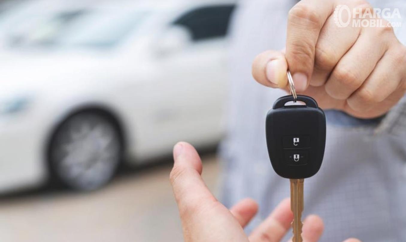 Gambar ini menunjukkan sebuah tangan memegang kunci mobil